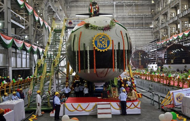 Employees stand near the Indian Navy's first indigenously-built Scorpene attack submarine at Mazagon Dock in Mumbai, India, Monday, April 6, 2015. Indian Defense Minister Manohar Parrikar and Maharashtra State Chief Minister Devendra Fadnavis Monday undocked the submarine from the dock, a naval vessel ship-building yard. (Photo by Rafiq Maqbool/AP Photo)