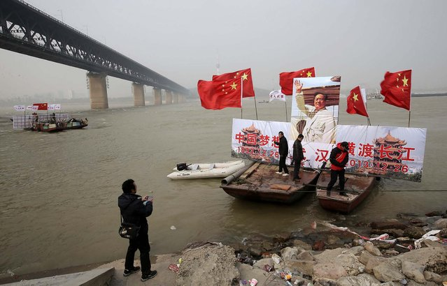 Boats in Wuhan, China, carrying a giant image of the late Chinese Chairman Mao Zedong and Chinese national flags, get ready to lead swimmers in an exercise in the Yangtze River to celebrate the 120th anniversary of Mao's birth, on December 26, 2013. (Photo by Reuters)