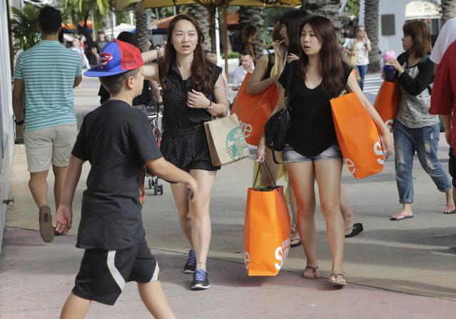 In this Wednesday, February 3, 2016, photo, tourists from Taiwan carry shopping bags as they walk along Lincoln Road Mall, a pedestrian area featuring retail shops and restaurants in Miami Beach, Fla. The Conference Board releases its February index on U.S. consumer confidence on Tuesday, Feb. 23, 2016. (Photo by Lynne Sladky/AP Photo)