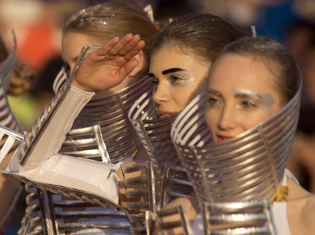 """Models promoting the Chinese movie """"Impossible"""" salute while wearing futuristic costumes as they arrive for the grand opening of the 5th annual Beijing International Film Festival in Beijing, Thursday, April 16, 2015. (Photo by Mark Schiefelbein/AP Photo)"""