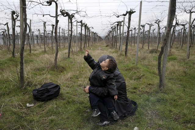 A migrant holds a child after crossing the Macedonian-Greek border in Gevgelija, Macedonia February 24, 2016. (Photo by Marko Djurica/Reuters)