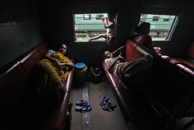 Passengers rest inside a train while waiting for the electricity to be restored at a railway station in Kolkata, July 31, 2012. (Photo by Rupak De Chowdhuri/Reuters)