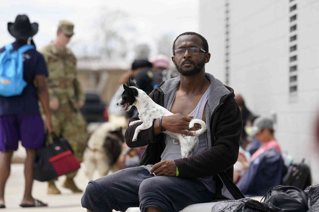 Galen Bell sits with his dog, Mason, after being rescued from floodwaters in the aftermath of Hurricane Ida in LaPlace, La., Monday, August 30, 2021. (Photo by Gerald Herbert/AP Photo)