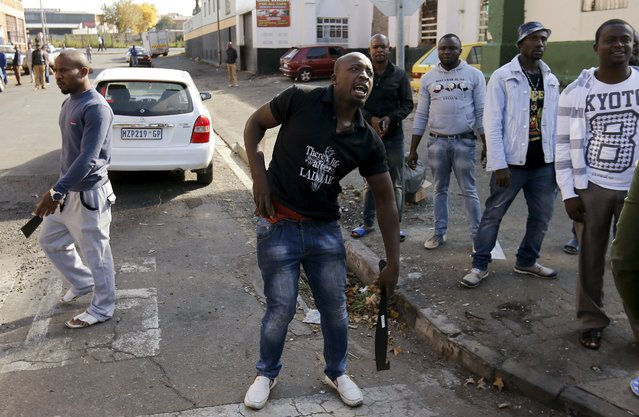 African immigrants carry machetes before being dispersed by police officers in Johannesburg, April 17, 2015. (Photo by Siphiwe Sibeko/Reuters)