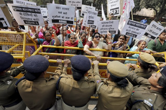 Activists from All India Democratic Women's Association (AIDWA) shout slogans behind a police barricade outside the Haryana Bhawan during a protest in New Delhi, India, February 29, 2016. Dozens of AIDWA activists on Monday held the protest demanding a probe into what they said were rapes and sexual assaults in Murthal town of Haryana state during more than a week of unrest involving the Jat rural caste demanding more government jobs and college places, according to the AIDWA activists. (Photo by Anindito Mukherjee/Reuters)
