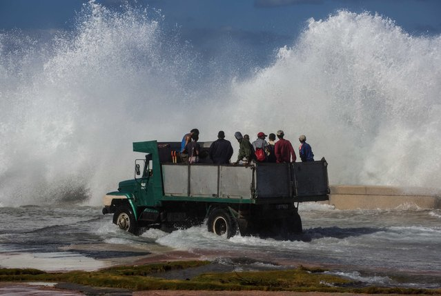 A dump truck carrying cleaning workers drives on Havana's malecon as a wave crashes on the sea wall, in Cuba, Tuesday, January 24, 2017. Due to high winds and tides, the sea pushed over the sea wall, flooding low parts of the Vedado neighborhood of Havana. (Photo by Desmond Boylan/AP Photo)