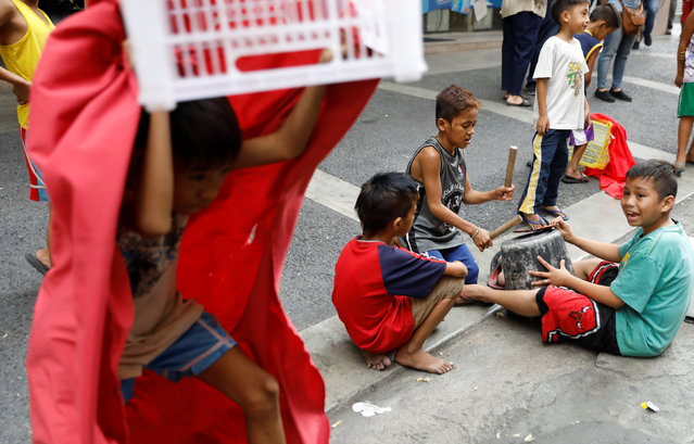 Children use makeshift drum and dragon dancer costume as they perform in the street on the eve of Lunar New Year in Manila's Chinatown, Philippines January 27, 2017. (Photo by Erik De Castro/Reuters)