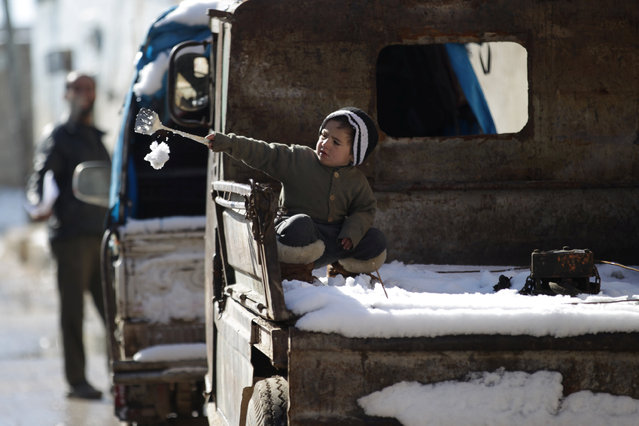 A child plays with snow on the back of a pick-up truck in al-Rai town, northern Aleppo countryside, Syria January 28, 2017. (Photo by Khalil Ashawi/Reuters)