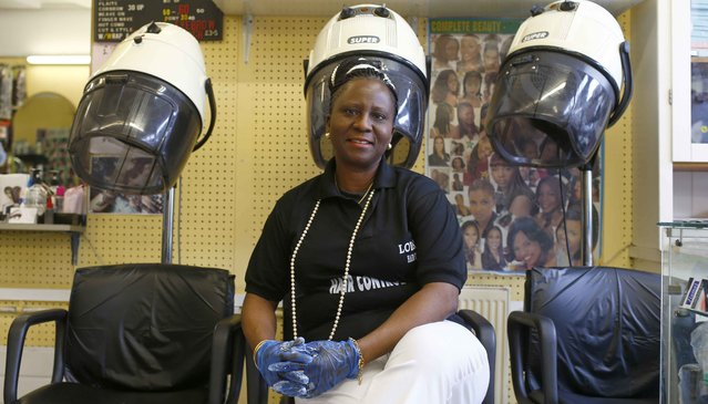 "Lola Ojewale, 55, poses for a photograph at her workplace, Hair Control Limited, in the London constituency of Brent Central, Britain, April 13, 2015. Ojewale was born in Nigeria and said: ""I've always voted Labour, I'm 100 percent behind them"". (Photo by Eddie Keogh/Reuters)"