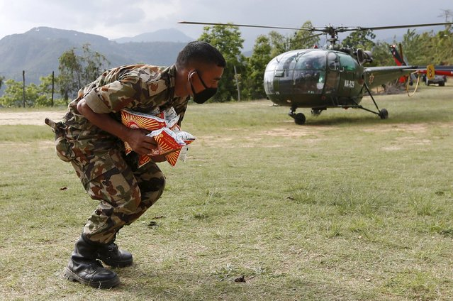 A Nepalese soldier loads food supplies at an army base in Chautara, Nepal, April 29, 2015. (Photo by Olivia Harris/Reuters)