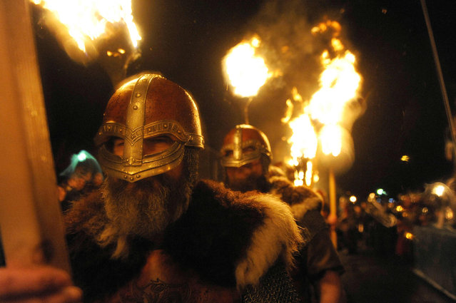 Participants dressed as Vikings carry torches as they march in procession before burning their viking galley ship at the culmination of the annual Up Helly Aa festival in Lerwick, Shetland Islands, on January 31, 2017. (Photo by Andy Buchanan/AFP Photo)