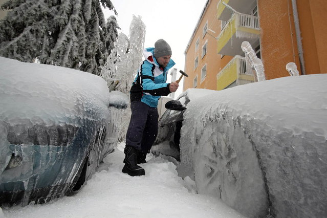 A man removes ice from an ice-covered car with a hammer in Postojna, Slovenia, on February 5, 2014. Cars stand entombed in a crystal-like casing near the deserted railway station in Postojna. Trees and electricity pylons lie felled in the snow by the sheer weight of ice enveloping them. (Photo by Srdjan Zivulovic/Reuters)