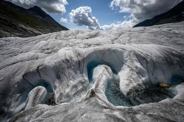 A picture taken on August 25, 2021 shows a view of the Aletsch Glacier. After hiking for hours across the mountain and a vast expanse of white, Swiss glaciologist Matthias Huss crouches down near the middle of the massive glacier and checks the measurements. Analysis of the data gathered from Aletsch, the largest glacier in the Alps, paints a dire picture of the toll that climate change is taking on the behemoth. (Photo by Fabrice Coffrini/AFP Photo)