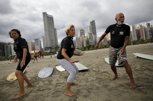 (L-R) Edmea Pereira, 69, Elsa Rodrigues, 61, and Osmidio Conde, 71, take part in their surf class in Santos, Sao Paulo state, Brazil, March 16, 2016. (Photo by Nacho Doce/Reuters)