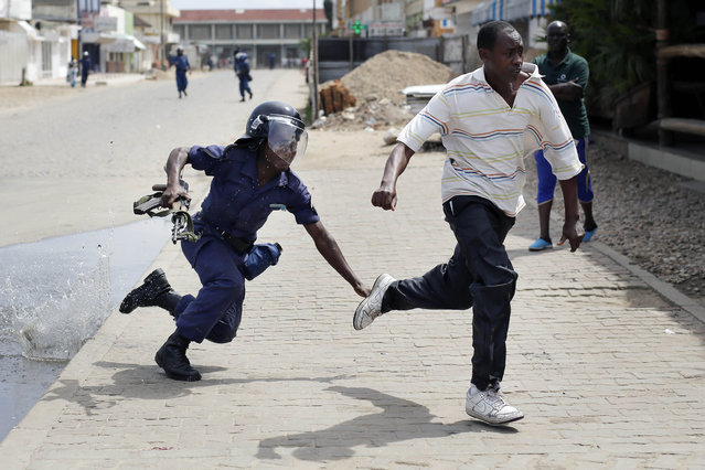 Riot police chase a demonstrator in Bujumbura, Burundi, Monday, May 4, 2015. (Photo by Jerome Delay/AP Photo)