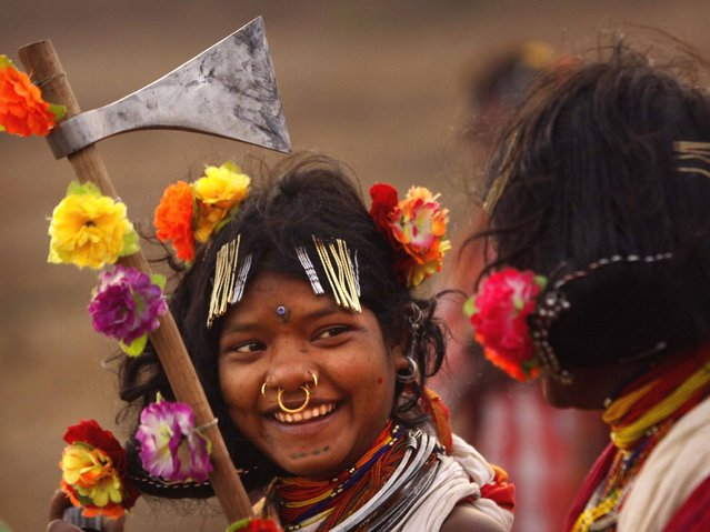 A Dongria tribe girl holds her traditional weapon and dance on the last day of their two days long Niyamraja Festival atop of the Niyamgiri hills near Lanjigarh in Kalahandi district, Orissa state. (Photo by Biswaranjan Rout/AP Photo)