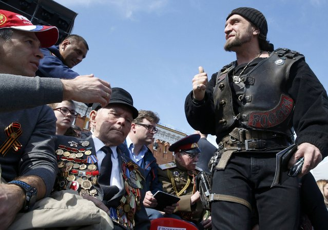 "Leader of the motorcycling club Night Wolves Alexander Zaldostanov (R), nicknamed ""Khirurg"" (Surgeon), gestures as he waits for the Victory Day parade at Red Square in Moscow, Russia, May 9, 2015. (Photo by Grigory Dukor/Reuters)"
