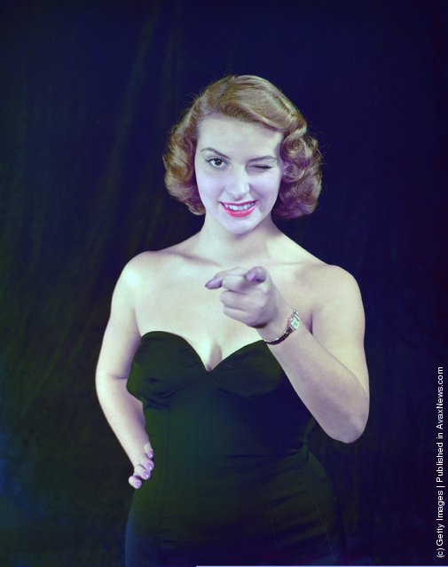 A portrait of a model pointing and winking at the camera, circa 1950