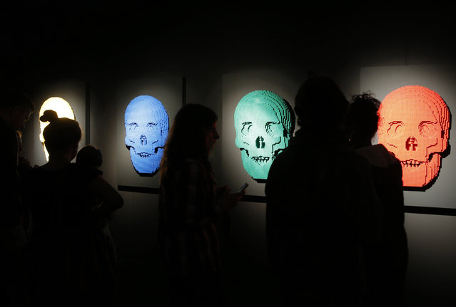 "Visitors watch ""Skuls"" a Lego sculpture by U.S. artist Nathan Sawaya presented during an exhibition The Art of the Brick, in Paris, France, Thursday May 14, 2015. (Photo by Christophe Ena/AP Photo)"