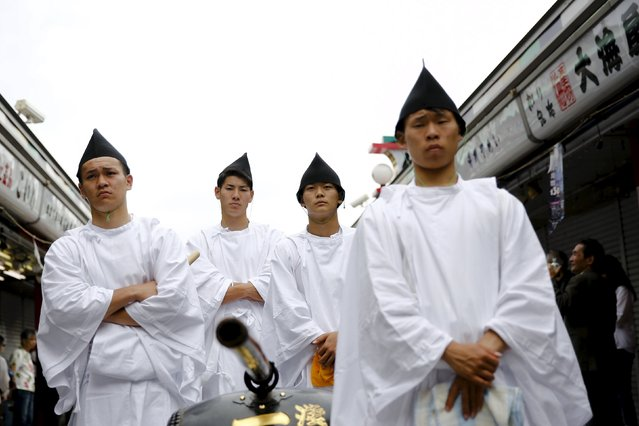 Men wearing Shinto dresses wait for the arrival of a portable shrine during the Sanja Matsuri festival in the Asakusa district of Tokyo May 17, 2015. (Photo by Thomas Peter/Reuters)