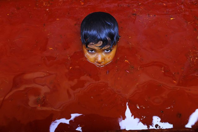 A boy plays in a pool of colored water at the Baldev Temple in Dauji, India, at the end of Holi celebrations, on March 18, 2014. The Baldev Temple is known for a ritual where the women playfully hit men with whips made of cloth as men throw buckets of water mixed with orange dye. (Photo by Rajesh Kumar Singh/Associated Press)
