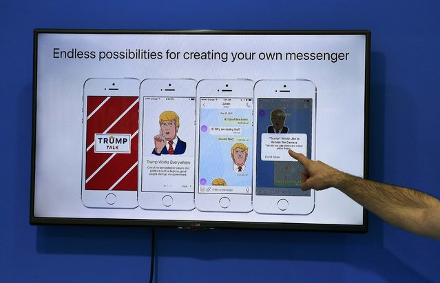 An exhibitor points to a display at the Zangi messenger app stand at the Mobile World Congress in Barcelona, Spain, February 28, 2017. (Photo by Paul Hanna/Reuters)