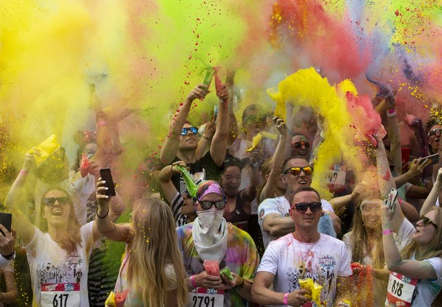 """Runners throw powdered paint powder after competing in the 5-kilometer (3-mile) """"Color Run"""" at the Luzhniki sports complex in Moscow, Russia, Sunday, June 2, 2019. Around 5,000 people participated in the fun run. (Photo by Alexander Zemlianichenko/AP Photo)"""