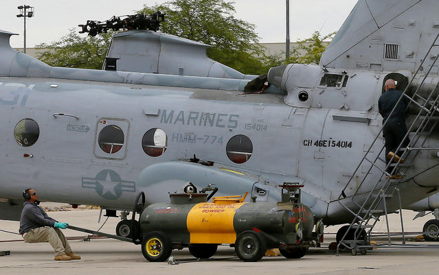 Crew from from the 309th Aerospace Maintenance and Regeneration Group boneyard prepare a pair Boeing Vertol CH-46 Sea Knight helicopters for storage after their arrival at Davis-Monthan Air Force Base in Tucson, Ariz. on Friday, May 15, 2015. The 309th is the United States Air Force's aircraft and missile storage and maintenance facility. AMARG provides long and short-term aircraft storage, parts reclamation and disposal. (Photo by Matt York/AP Photo)