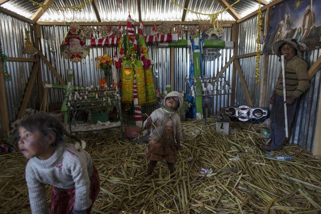 In this February 2, 2017 photo, children play inside a church in Kapi Cruz Grande, a community on the shores of Lake Titicaca in the Puno region of Peru. Many living on the 4,000-meter (13,100-feet) high plain surrounding the lake contaminated with toxic levels of lead and mercury feel government leaders have neglected them. (Photo by Rodrigo Abd/AP Photo)