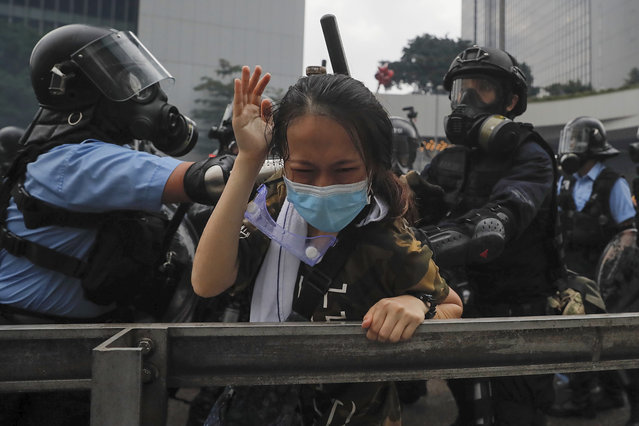 In this Wednesday, June 12, 2019, file photo, a protester reacts as she tackled by riot police during a massive demonstration outside the Legislative Council in Hong Kong. (Photo by Kin Cheung/AP Photo/File)