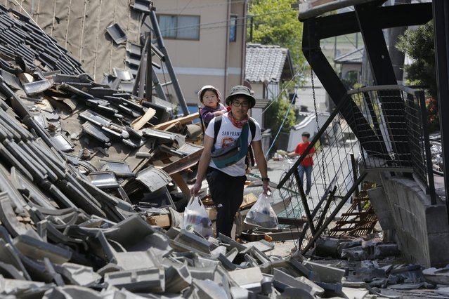 A resident carrying his child on his back walks through debris of collapsed houses with supplies following a magnitude 6.2 earthquake, intensity seven on the Japan Meteorological Agency seismic intensity scale; the first intensity seven since the 2011 Tohoku earthquake and tsunami, in Mashiki town, Kumamoto Prefecture, southwestern Japan, 15 April 2016. Strong earthquakes hit southwestern Japan the evening of 14 April. Authorities said at least nine people died and over 1,000 were injured by the earthquake, now named the Kumamoto Earthquake. Eight of the nine victims were reported in the town of Mashiki. (Photo by Kimimasa Mayama/EPA)