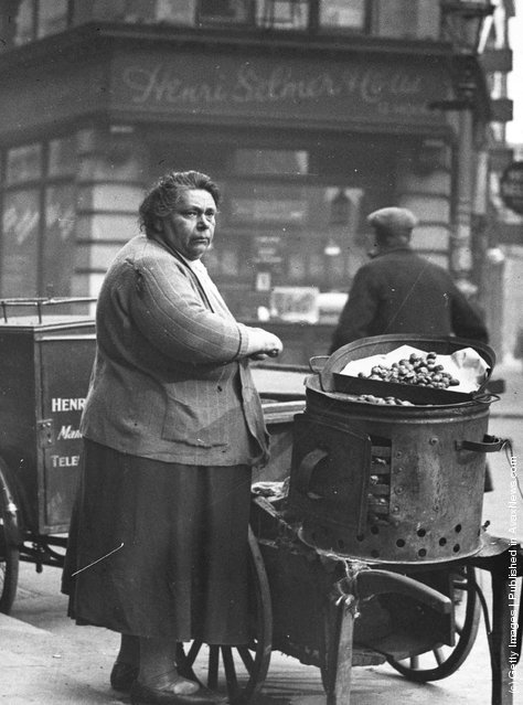 1935: A miserable looking woman selling hot chestnuts in a Soho street