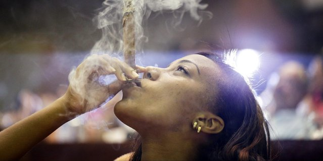 A woman smokes a Montecristo cigar during a cigar smoker's competition for the longest ash, during the 17th Habanos tobacco festival, on February 26, 2015 in Havana, Cuba. The festival is held every year and will culminate in a gala dinner with an auction of humidors on Friday. After the latest developments in the relationships between Cuba and the Uniteed States, Americans are now allowed to import Cuban cigars up to $100 USD. The second round of talks about re-establishing diplomatic relations between both governments will take place on February 27 in Washington. (Photo by Sven Creutzmann/Mambo Photo/Getty Images)