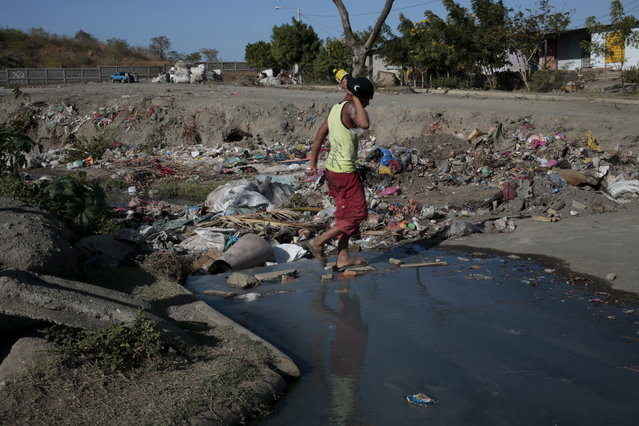 A boy walks over a polluted canal at outskirts of Managua, Nicaragua on January 27, 2016. Nicaraguan government spokeswoman Rosario Murillo announced on Thursday of a new positive case of Zika in Managua city, bringing confirmed cases in the country to three. (Photo by Oswaldo Rivas/Reuters)