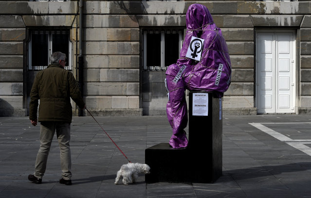 A man and his dog walk past the sculpture of a woman covered in paper and ropes as part of a performance to protest the lack of visibility of women in public spaces, on International Women's Day in Oviedo, Spain, March 8, 2017. The covered statue is La Pensadora (The female Thinker) by Spanish artist Jose Luis Fernandez. (Photo by Eloy Alonso/Reuters)