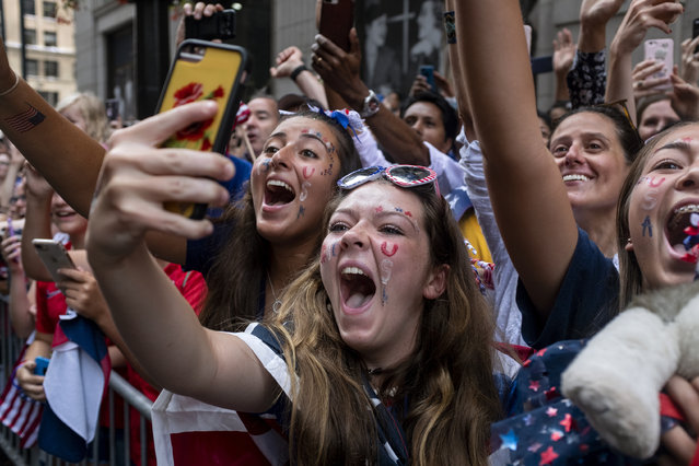 Fans celebrates as members of the the U.S. women's soccer team pass by during a ticker tape parade along the Canyon of Heroes, Wednesday, July 10, 2019, in New York. The U.S. national team beat the Netherlands 2-0 to capture a record fourth Women's World Cup title.(Photo by Craig Ruttle/AP Photo)