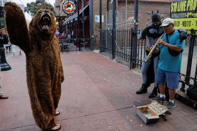 People in costume interrupt a street performer as during the opening night of the pop culture festival Comic Con International in San Diego, California,U.S., July 17, 2019. (Photo by Mike Blake/Reuters)