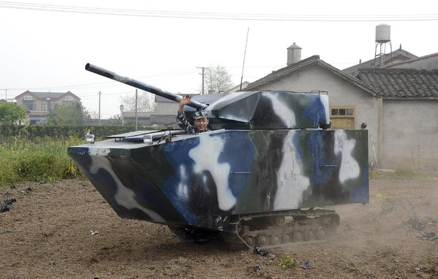 """Jian Lin, a 31-year-old farmer who used to serve in the Chinese navy, waves in his home-made replica of a tank during a trial run, at a village in Mianzhu, Sichuan province April 9, 2014. The """"tank"""", which measures 4.5m long (15 feet), 1.6m wide (5 feet) and 2.1m high (7 feet), weighs nearly 3 tons and cost Jian about 40,000 yuan ($6,450) to make, local media reported. (Photo by Reuters/Stringer)"""