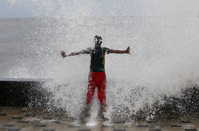 A boy gets drenched in a large wave during high tide at a sea front in Mumbai, India, June 15, 2015. (Photo by Danish Siddiqui/Reuters)