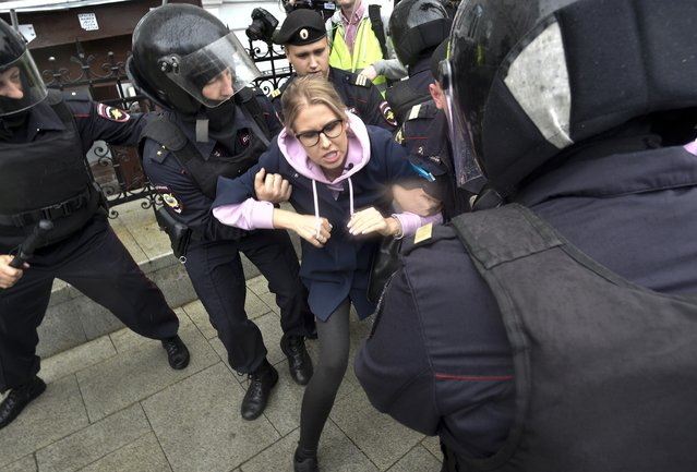 Police officers detain an opposition candidate and lawyer at the Foundation for Fighting Corruption Lyubov Sobol in the center of Moscow, Russia, Saturday, August 3, 2019. Moscow police detained more than 300 people Saturday who are protesting the exclusion of some independent and opposition candidates from the city council ballot, a monitoring group said. (Photo by Dmitry Serebryakov/AP Photo)