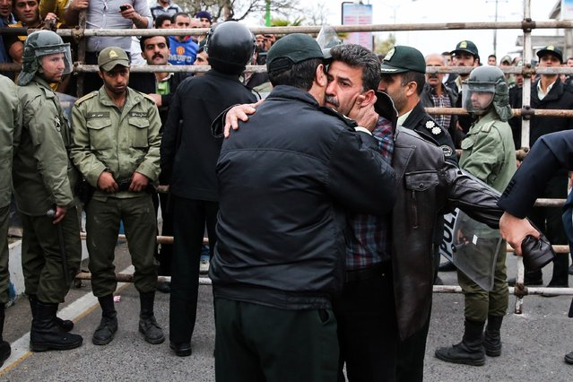 A police office kisses Abdolghani Hosseinzadeh (C-R) the father of Abdolah Hosseinzadeh who was killed by a fellow Iranian, named Balal, in a street fight with a knife in 2007, during Balal's execution ceremony in the northern city of Nowshahr on April 15, 2014. Samereh Alinejad, the mother of Abdolah Hosseinzadeh spared the life of Balal, her son's convicted murderer, with an emotional slap in the face as he awaited execution prior to removing the noose around his neck. (Photo by Araash Khamooshi/AFP Photo/ISNA)