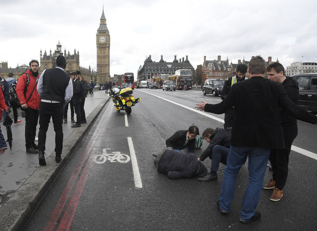 An injured person is assisted after an incident on Westminster Bridge in London, Britain on Wednesday, March 22, 2017. (Photo by Toby Melville/Reuters)