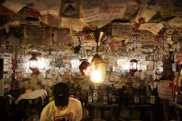 A bartender fixes a drink in a bar decorated with thousands of messages written by patrons at the Golden Gai in the Shinjuku district of Tokyo, July 26, 2019. (Photo by Jae C. Hong/AP Photo)