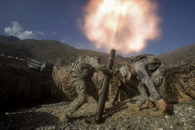 U.S. soldiers from the 2nd Battalion, 12th Infantry Regiment, 4th Brigade Combat Team, fire mortars at known enemy firing positions from a base in the Pech River Valley in Afghanistan's Kunar province, Saturday, October 24, 2009. (Photo by David Guttenfelder/AP Photo)