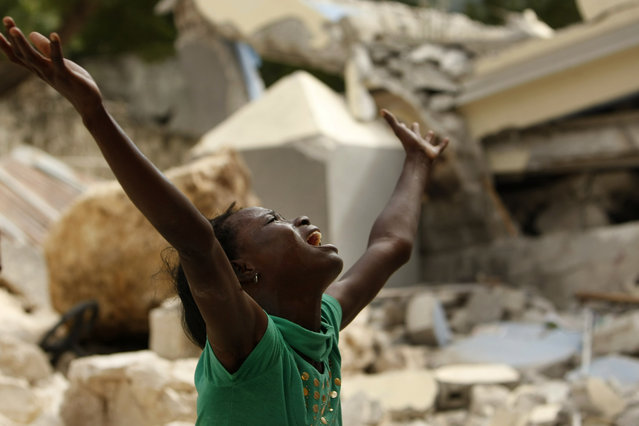 Cindy Terasme screams after seeing the feet of her dead 14-year-old brother Jean Gaelle Dersmorne in the rubble of the collapsed St. Gerard School in Port-au-Prince, Haiti, Thursday, January 14, 2010, after 7.0-magnitude earthquake. (Photo by Gerald Herbert/AP Photo)