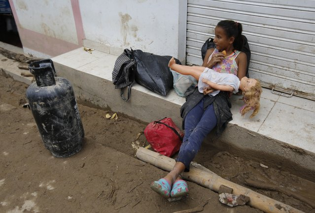 A girl holds a doll rescued from her damaged house in Mocoa, Colombia, Sunday, April 2, 2017. A grim search for the missing resumed at dawn Sunday in southern Colombia after surging rivers sent an avalanche of floodwaters, mud and debris through a city, killing at least 200 people and leaving many more injured and homeless. (Photo by Fernando Vergara/AP Photo)