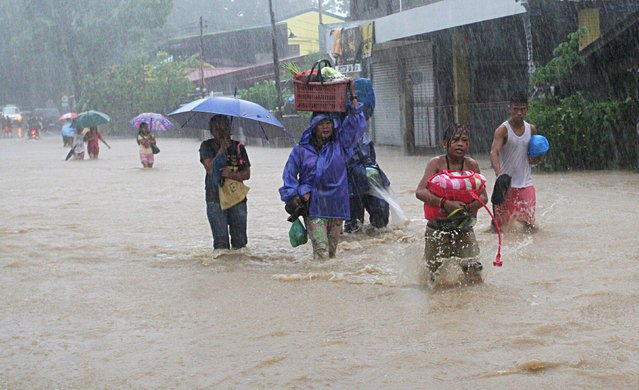 Residents wade along a flooded road after tropical storm Linfa hit San Fernando, La Union in northern Philippines July 5, 2015. (Photo by T. J. Corpuz/Reuters)
