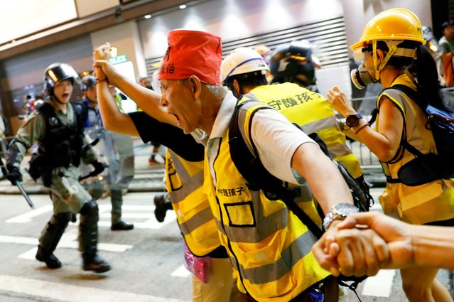 A man tries to block riot police during a protest near Mong Kok police station in Hong Kong, China on September 7, 2019. (Photo by Tyrone Siu/Reuters)