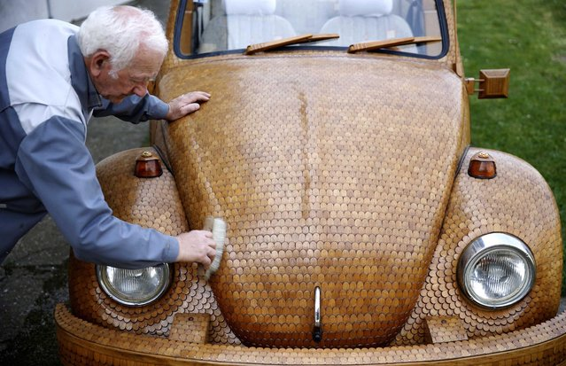 Bosnian pensioner Momir Bojic cleans his wooden Volkswagen Beetle car in front of his home in Celinac near Banja Luka, April 2, 2014. Bojic,71, an avid Volkswagen fan, created the car from over 50,000 separate pieces of oak and took two years to complete it. German carmaker Volkswagen posted a quarterly jump in operating profit as Europe's fledgeling economic recovery lifted sales of Audi and Porsche luxury models to record levels. (Photo by Dado Ruvic/Reuters)