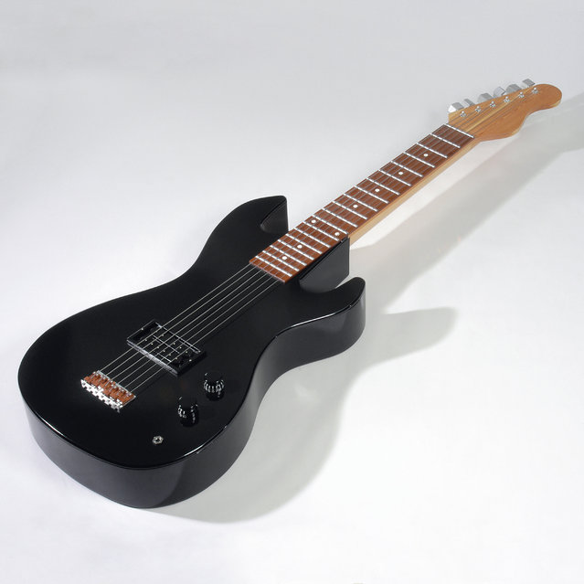 A coffin in the shape on a guitar. (Photo by Caters News Agency)